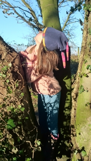 girl-in-pink-jumper-blue-leggings-and-woolly-hat-amongst-ivy-covered-tree-trunks