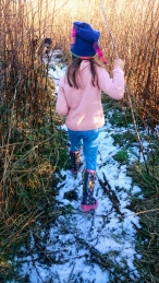 girl-in-pink-jumper-blue-leggings-and-woolly-hat-walking-through-reeds-with-snow-on-ground