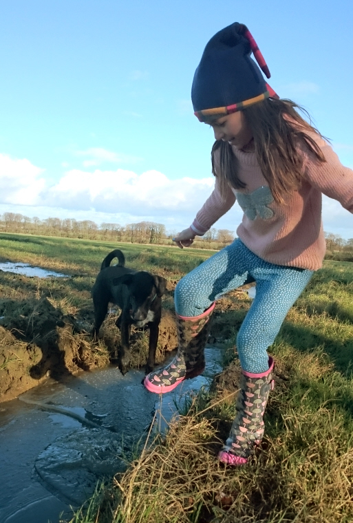 girl-with-dog-jumping-on-frozen-puddles-in-tractor-tracks