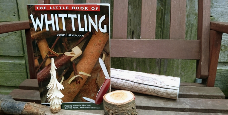 little-book-of-whittling-book-with-wood-logs-and-mini-carved-tree-on-bench-in-front-of-fence