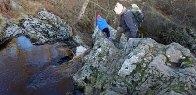 man-and-girl-climbing-on-rocks-near-top-of-waterfall