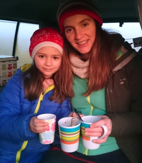 woman and-child-wearing-winter-outdoor-gear-in-vehicle-holding-mugs