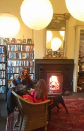 woman-child-and-dog-sitting-in-front-of-open-fire-with-bookshelves-behind