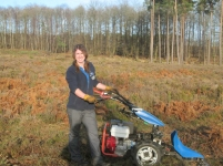 woman-in-field-with-woods-behind-using-machinery-cutter