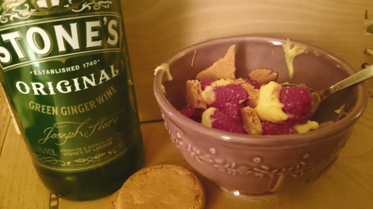 bottle-of-ginger-wine-next-to-red-bowl-of-custard-raspberries-and-ginger-biscuits