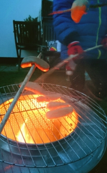 close-up-of-sausages-cooking-on-firepit-in-washing-machine-drum
