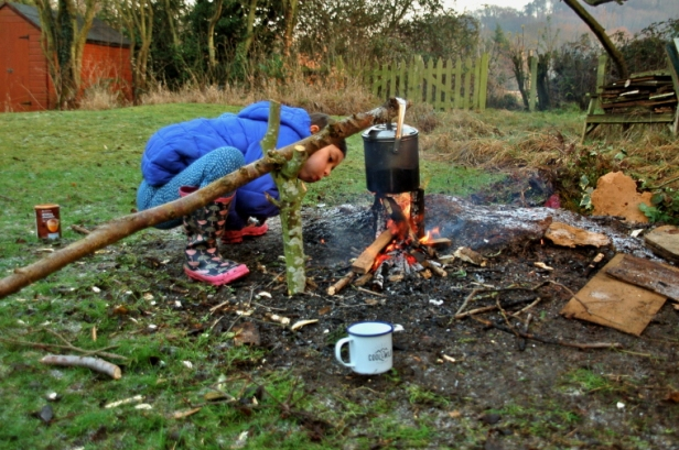 girl-blowing-flames-on-fire-in-back-garden-with-cookpot-on-sticks