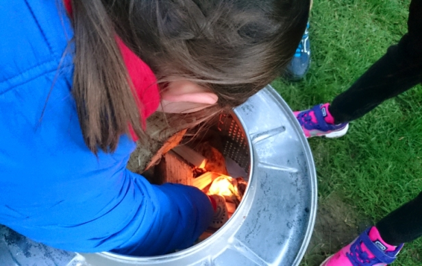 girl-lighting-fire-with-match-inside-washing-machine-drum