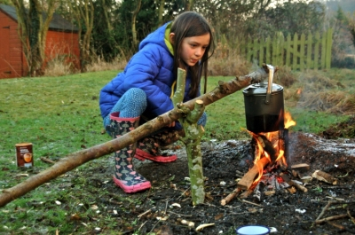 girl-looking-at-pot-cooking-on-camp-fire-in-garden