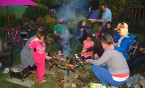 group-of-people-and-children-around-firepit-in-garden