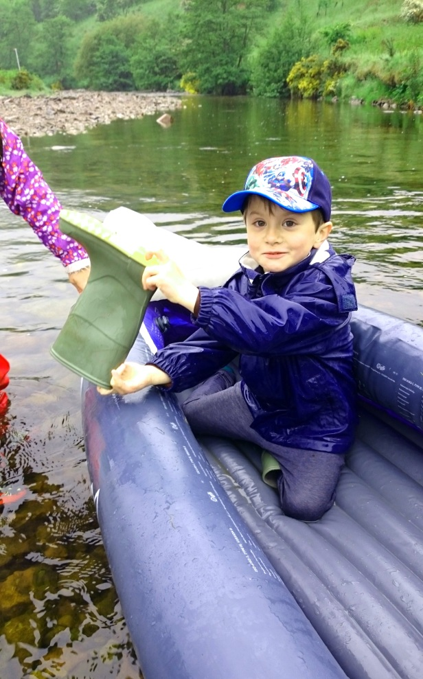 Boy in iflatable canoe bailing out with a welly boot
