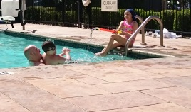Girl at pool edge firing water pistol at man and boy in pool