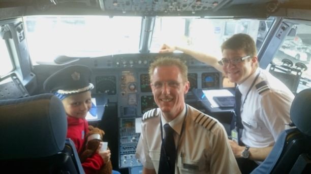 Girl in pilot's hat with 2 pilots in BA aircraft cockpit