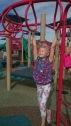 Girl on monkey bars at play park