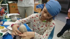 Girl pressing plastic fibre around teddy bear's head