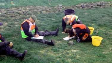 Image of IFCA officers in florescent jackets on grass measuring and recording catch details during a fish survey on the Aln