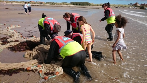Image of workers in IFCA jackets collecting fish from net on beach