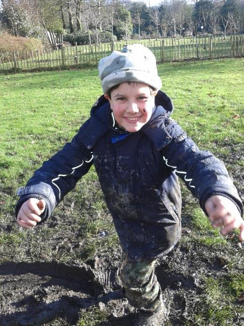 Boy in field covered in mud