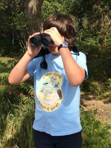 Boy in woods with binoculars