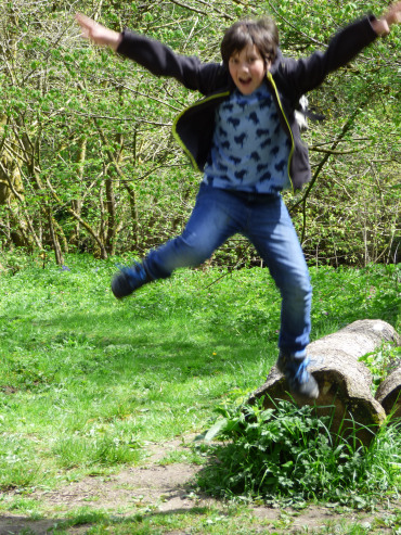 Boy leaping off a log