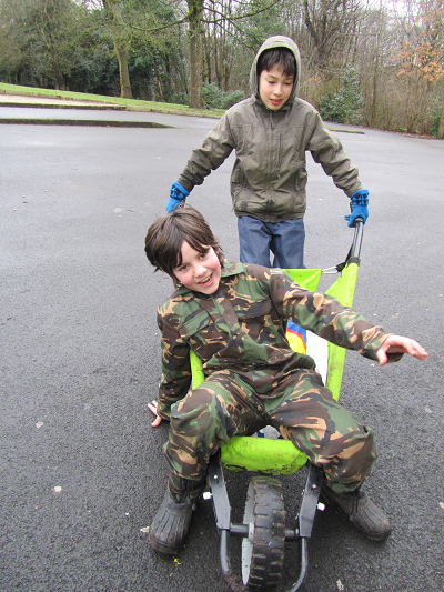 Boy pushing another boy in wheelbarrow