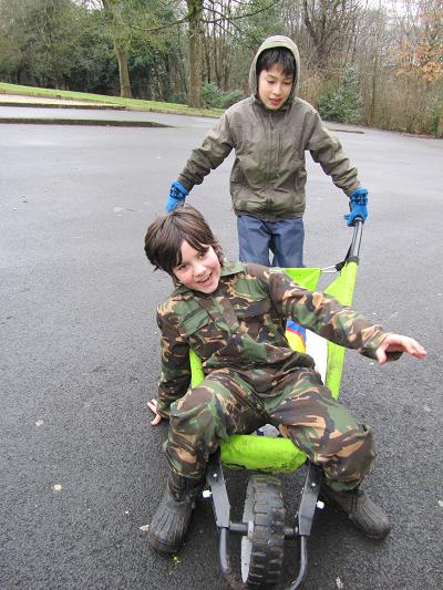 Boy pushing another boy in wheelbarrow