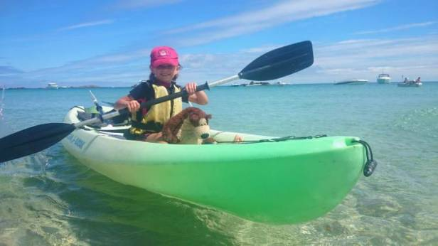 Girl in wetsuit and buoyancy aid with brown and cream bear in green kayak paddling in clear water