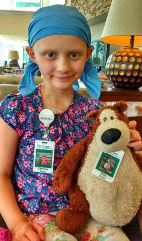 Girl with no hair in bandana with teddy bear, both with ID badges