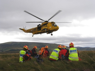 Yello RAF rescue helicopter with Northumberland National Park Mountain Rescue Team members on ground