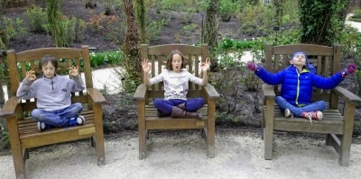 Three children each sitting on wooden seat in garden in meditation pose