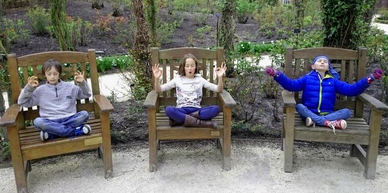 Three children each sitting on wooden seat in garden in meditation pose