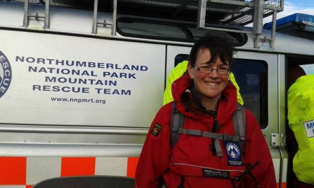 Woman in red outdoor gear in front of Northumberland National Park Mountain Rescue Team vehicle