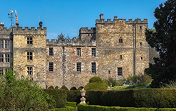 Image of rear view of Chillingham Castle with flower borders and knot garden in foreground