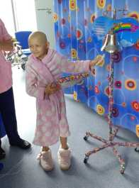 Image of girl in dressing gown ringing bell on a stand with bright patterned hospital curtains behind