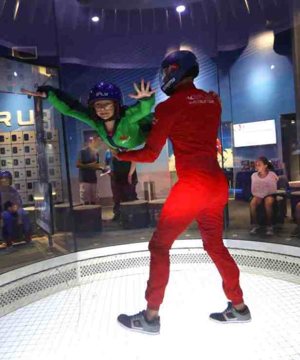 Image of girl in green flying suit being held by man in red flying suit in sky diving practice wind tunnel