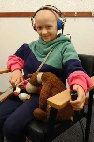 Image of girl with no hair holding teddy bear sitting in chair wearing headphones and holding press button