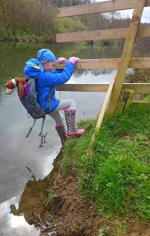 Image of child in blue coat and blue bandana climbing around fence over river wearing backpack with teddy bear inside