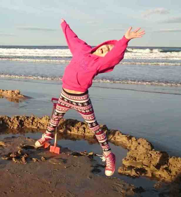 Image of girl on beach jumping for joy