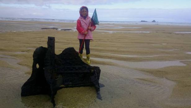 Image of girl standing on metal piece of shipwreck on rainy beach with rock islands in background