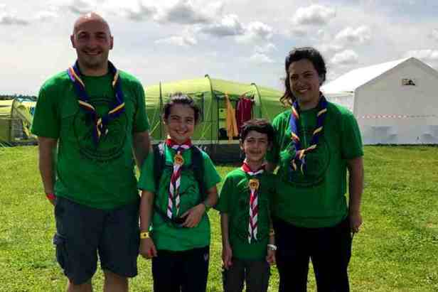 Image of man, woman, girl and boy in green scout uniforms in front of tents in field