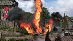 Image of explosion and flames with prow of Viking ship in foreground