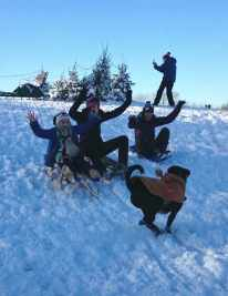 Image of 3 girls on sledge about to crash into black dog on short gentle snowy slope with blue sky behind