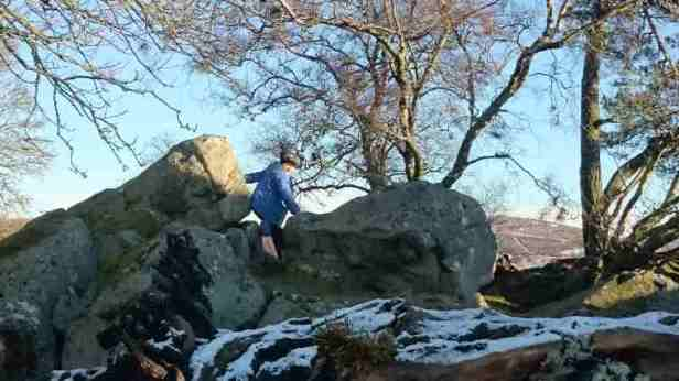 Image of child in blue jacket scrambling in rocky crags with light snow on ground