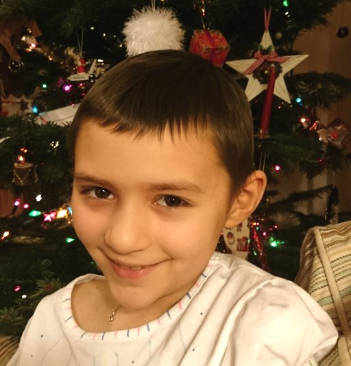 Image of close up of smiling girl with short Audrey Hepburn haircut and white T-shirt in front of Christmas tree