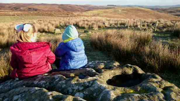 Image of girl in red jacket and child in blue jacket sitting on large rock looking at moorland view behind