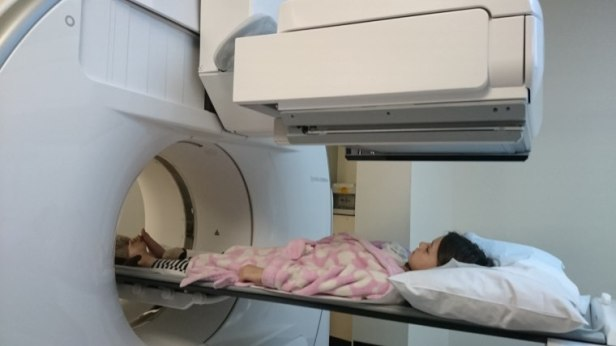 Image of girl wearing dressing gown lying underneath gamma ray scanner