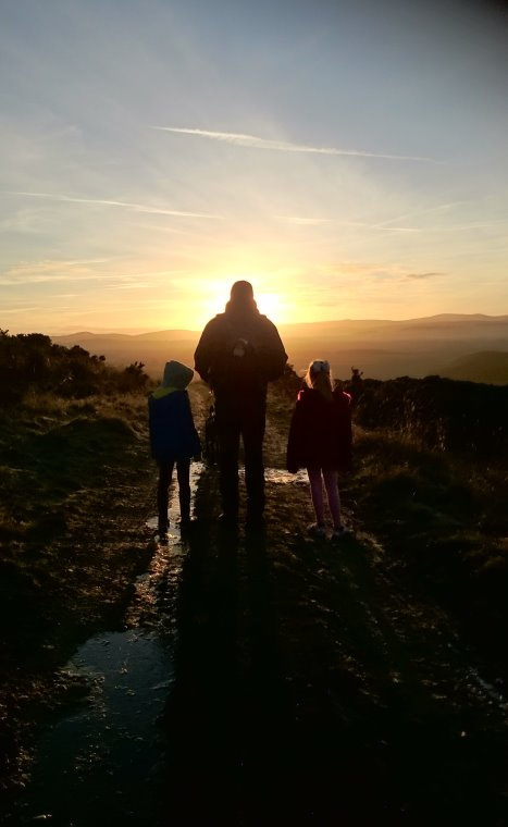 Image of man and two children silhouetted against sunset in walled country field with hills in background