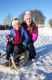 Image of mother and child on wooden sledge on bright snowy hillside with tower in background and blue sky