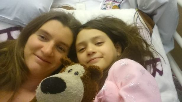 Image of mother and child's faces lying on hospital bed with teddy bear photo bombing at middle front