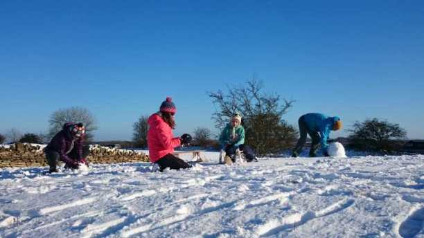 Image of three adults and one child kneeling in snow making snowballs with sunny blue sky behind